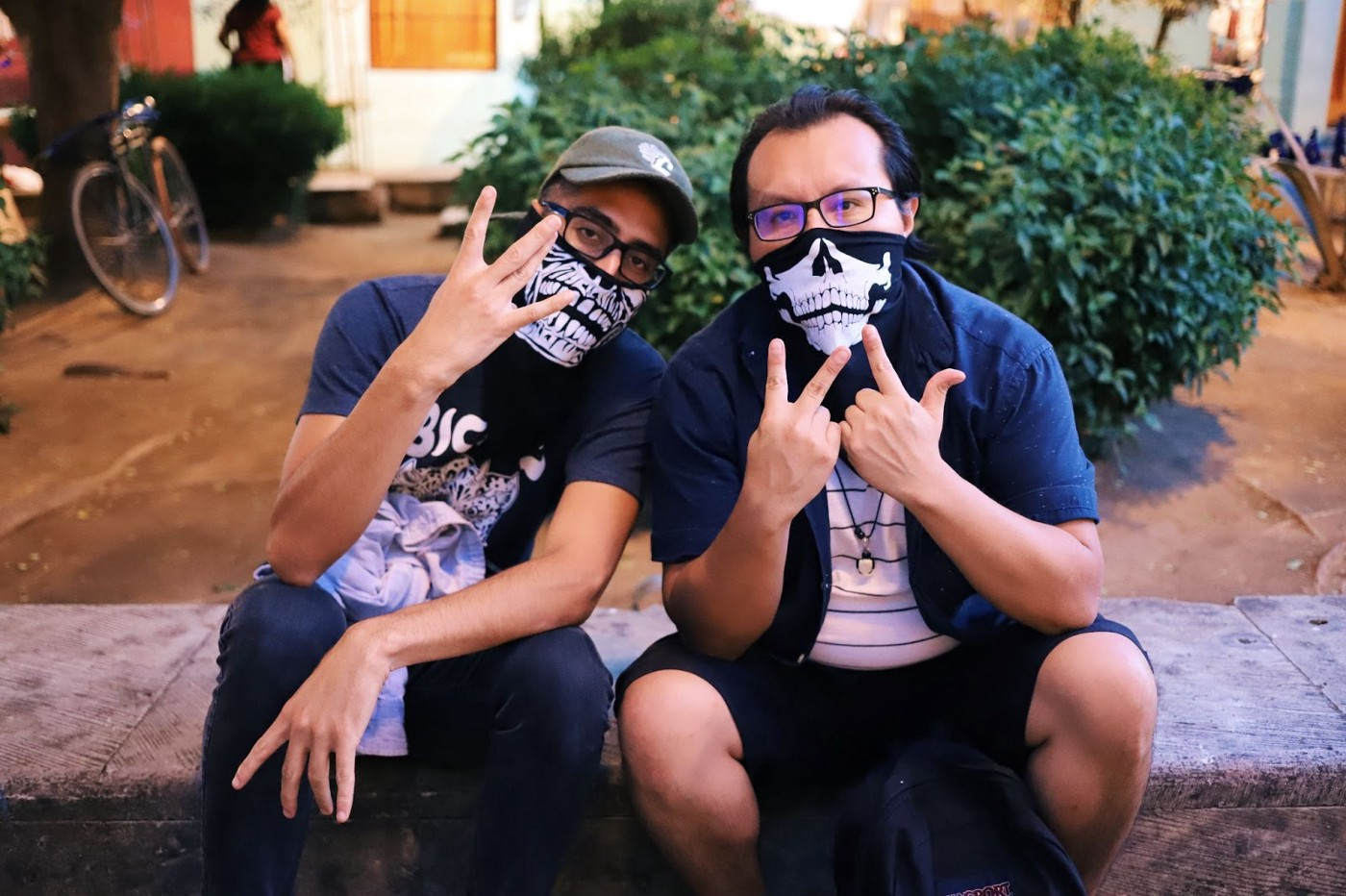 Two people wearing skull gaiters on their faces, holding fingers in W shapes, sitting on a stone bench in front of a house at night.