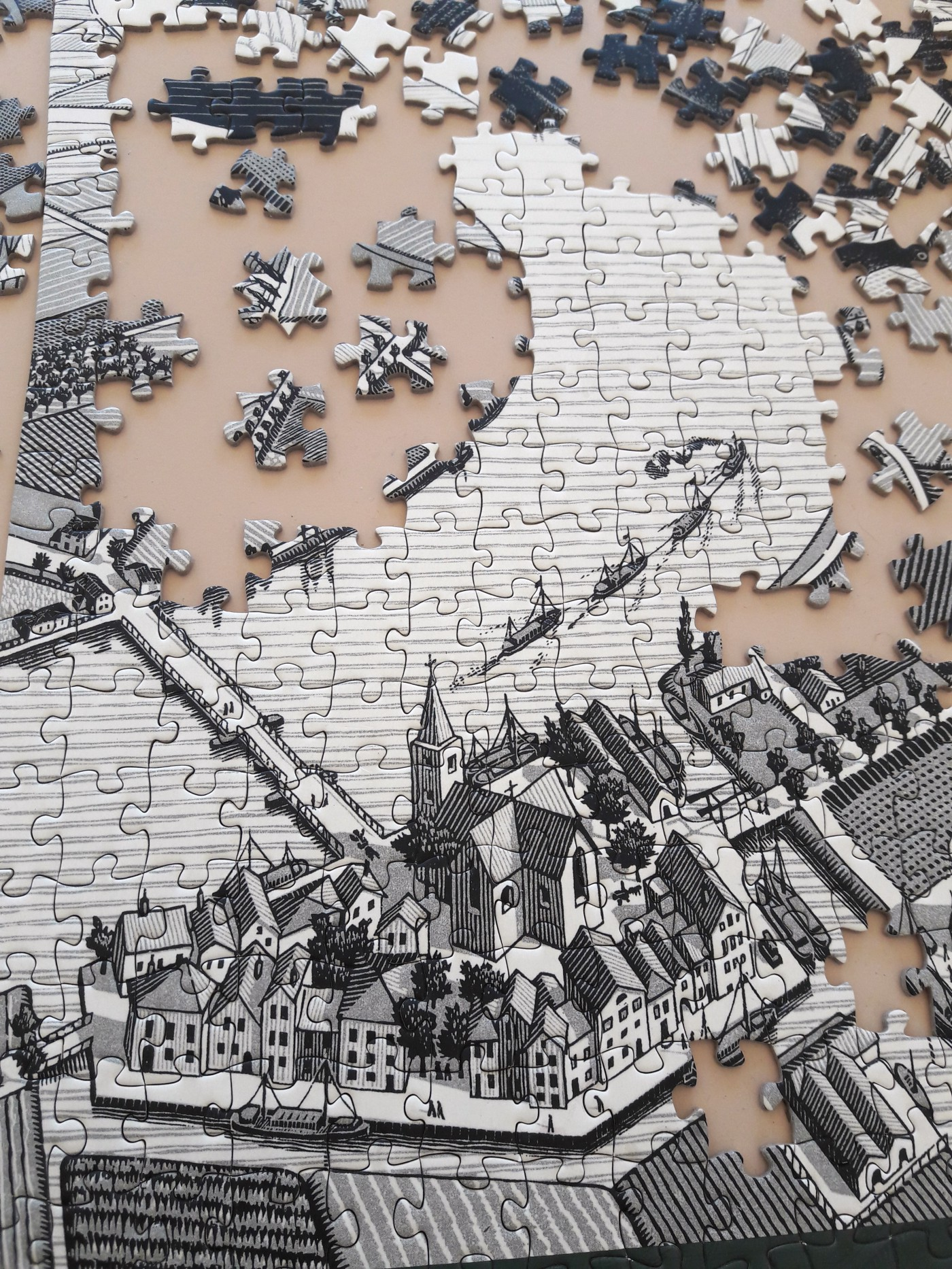 Partially completed puzzle with remaining puzzle pieces scattered around it. Black and white.