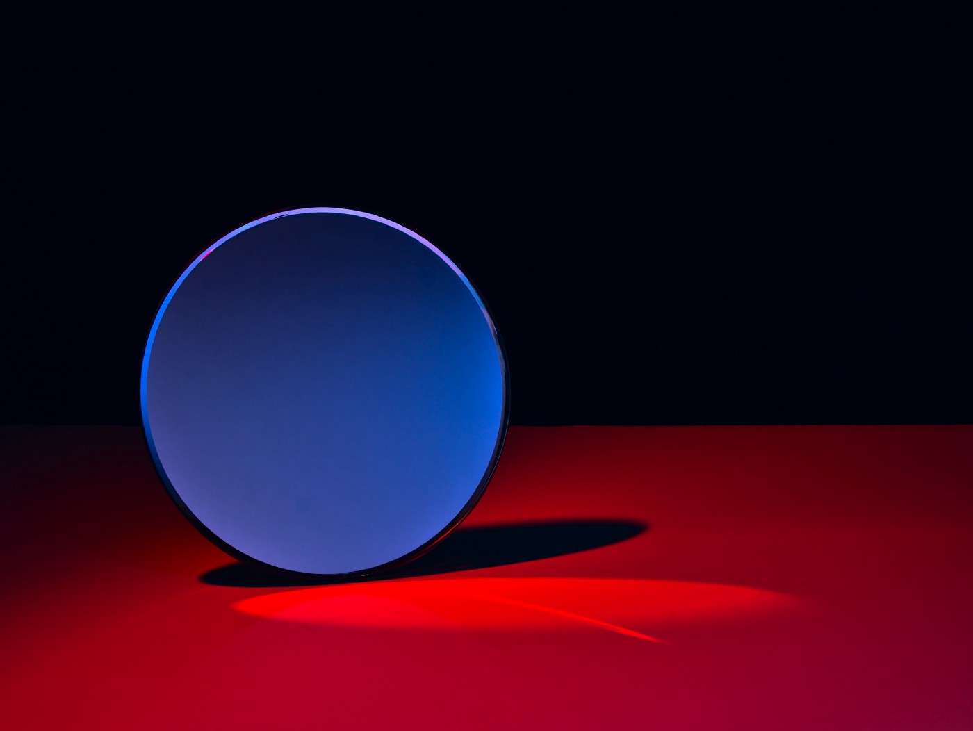 decorative: blue disc standing edgewise on a red surface against a black background