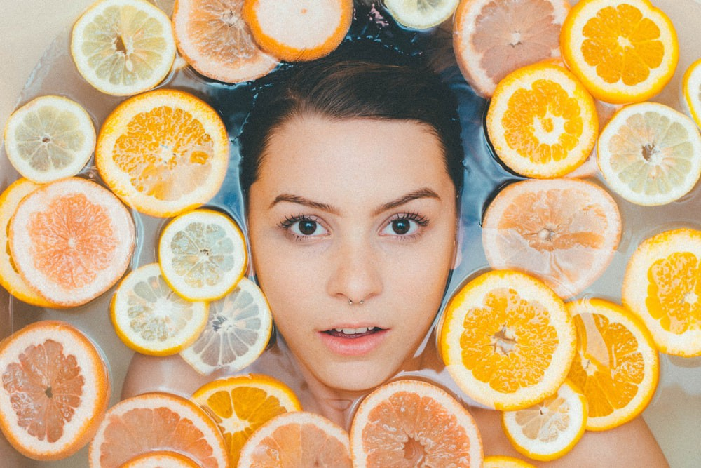Face emerging from a bath with orange slices floating in it.