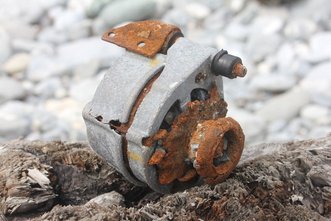 a rust-covered machinery part sitting on rocks