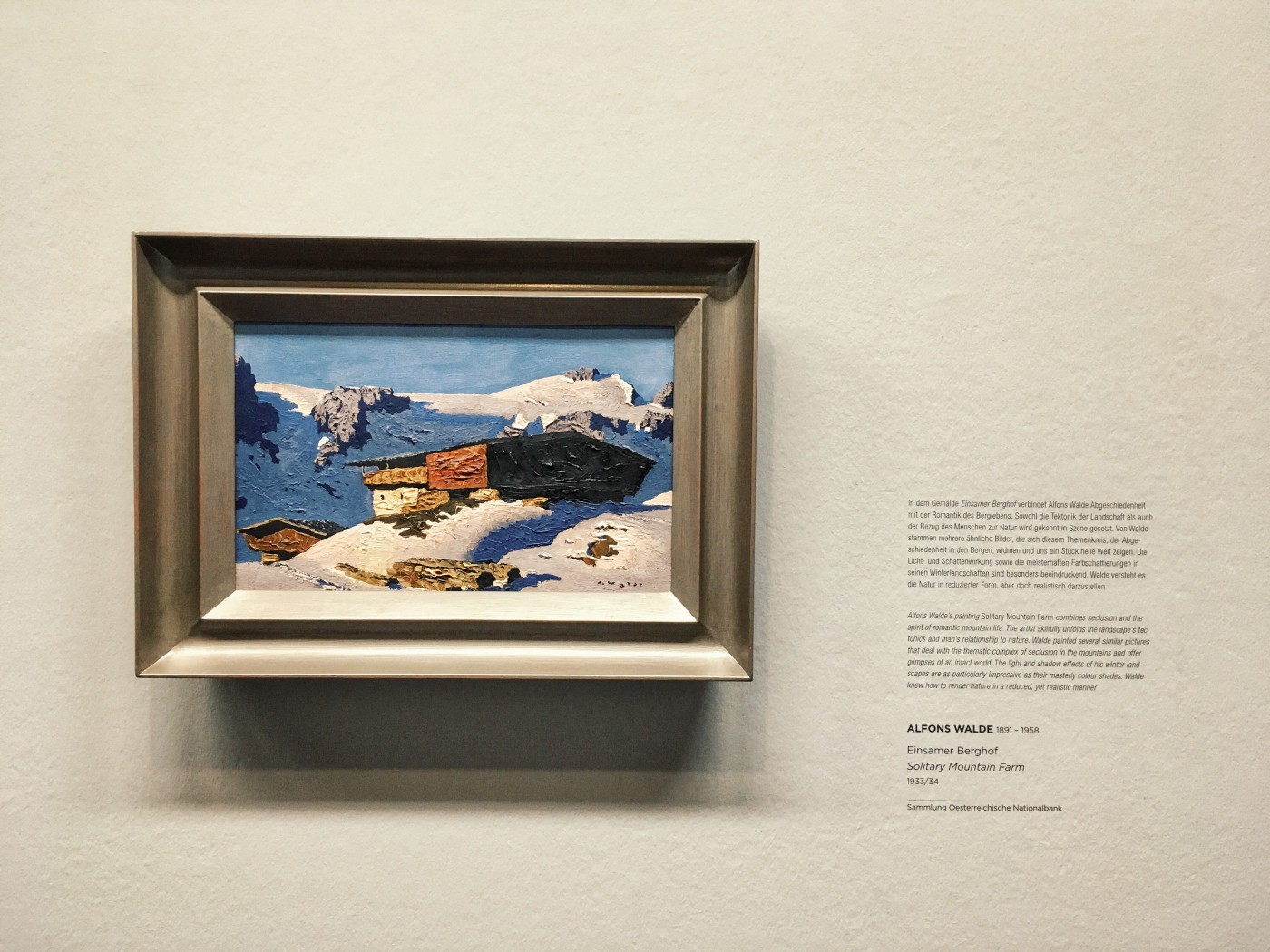 The art painting presenting home in mountains in the winter on the museum wall. On the right side of the picture there is a long description about the image.
