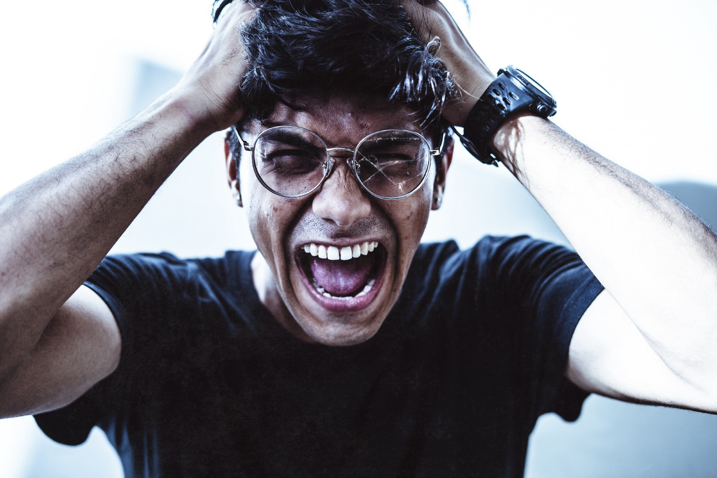 A young man is wearing glasses and a black shirt as he screams in anger for making the number one mistake of judgment after having a story go viral.