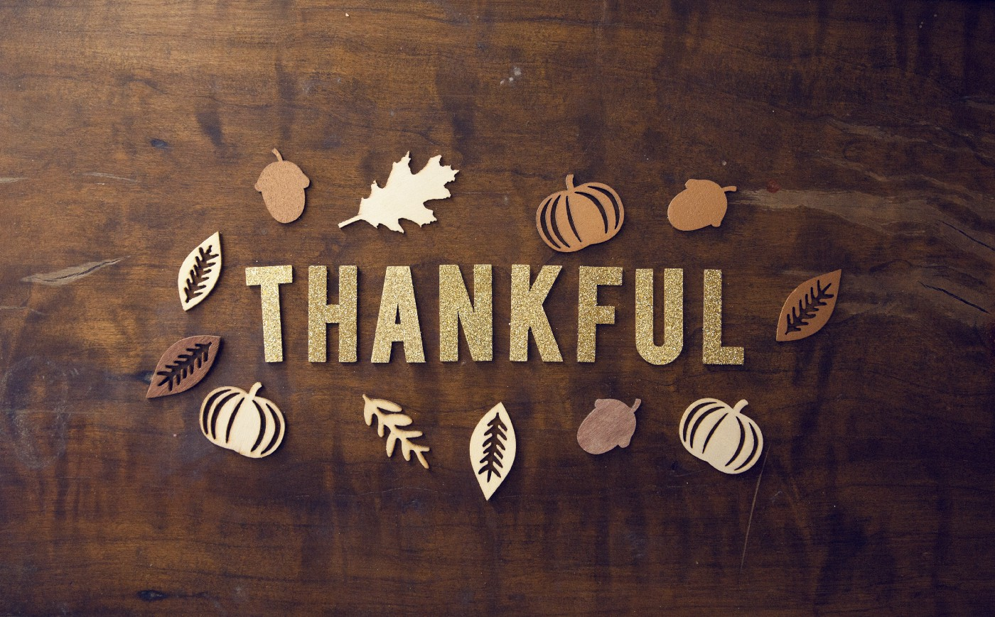 "The word ""Thankful"" spelled out on a wooden surface, surrounded by paper cutouts of leaves, acorns, and pumpkins"