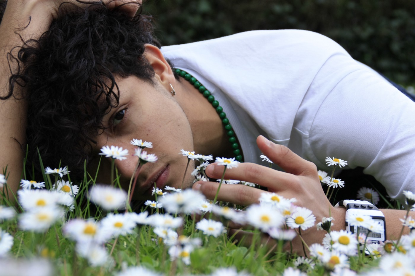 teen boy laying in daisies solumnly looking into camera