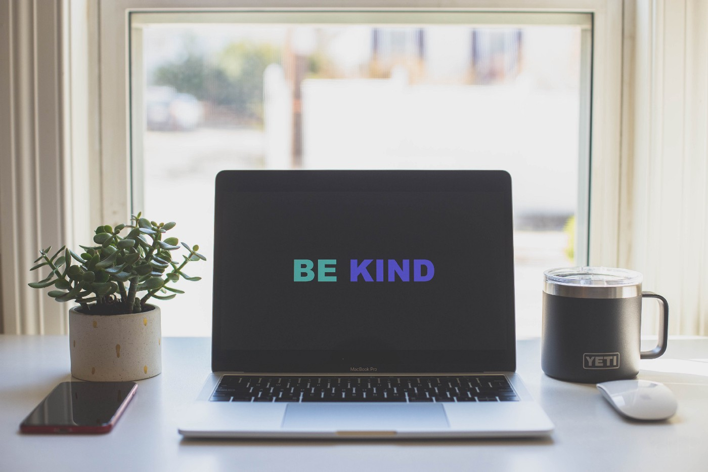 """A desk with a laptop in the middle with the words """"BE KIND"""" on the screen."""
