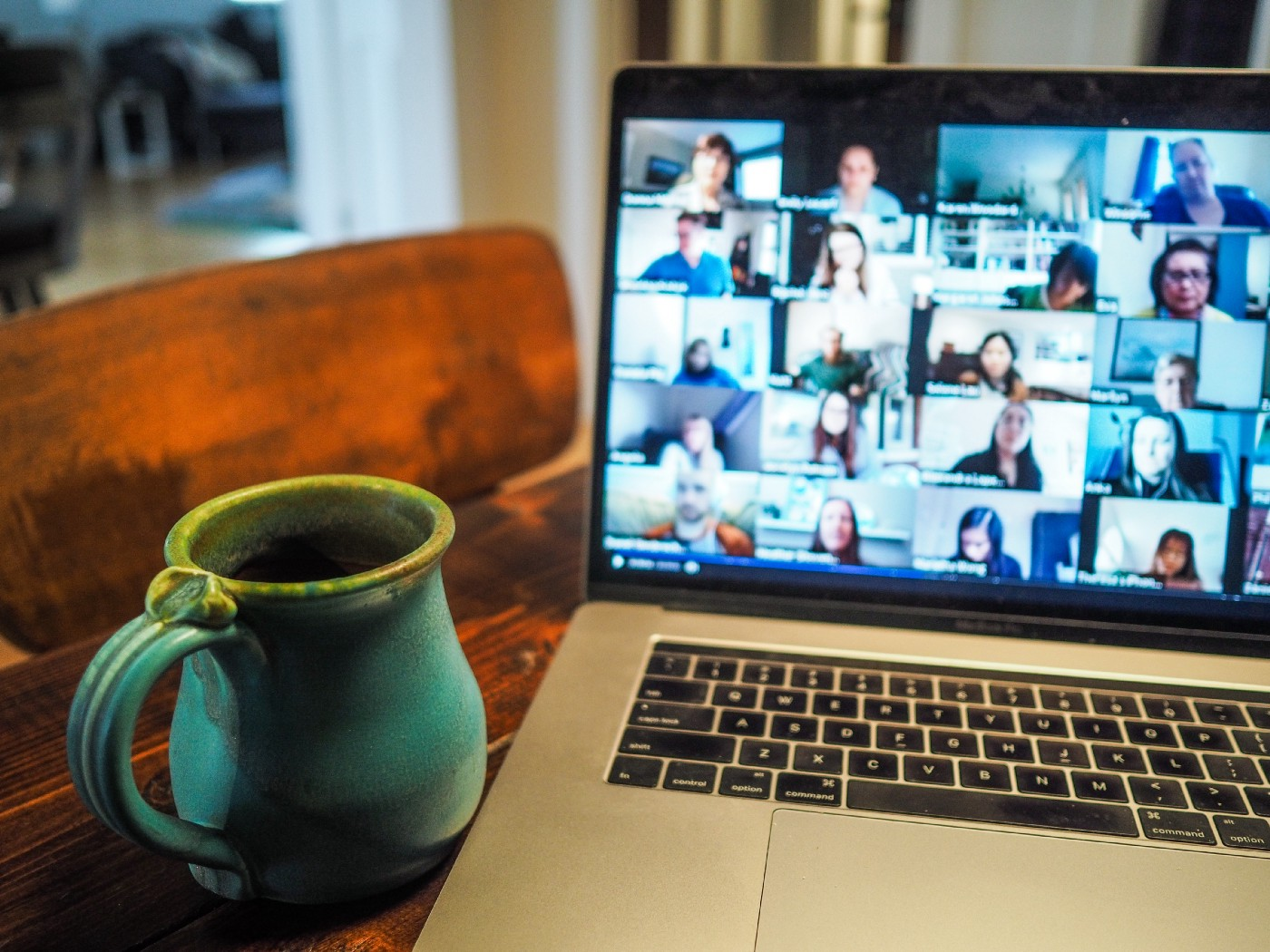 A laptop computer, with a mug beside it, shows many faces in a Zoom online conference.