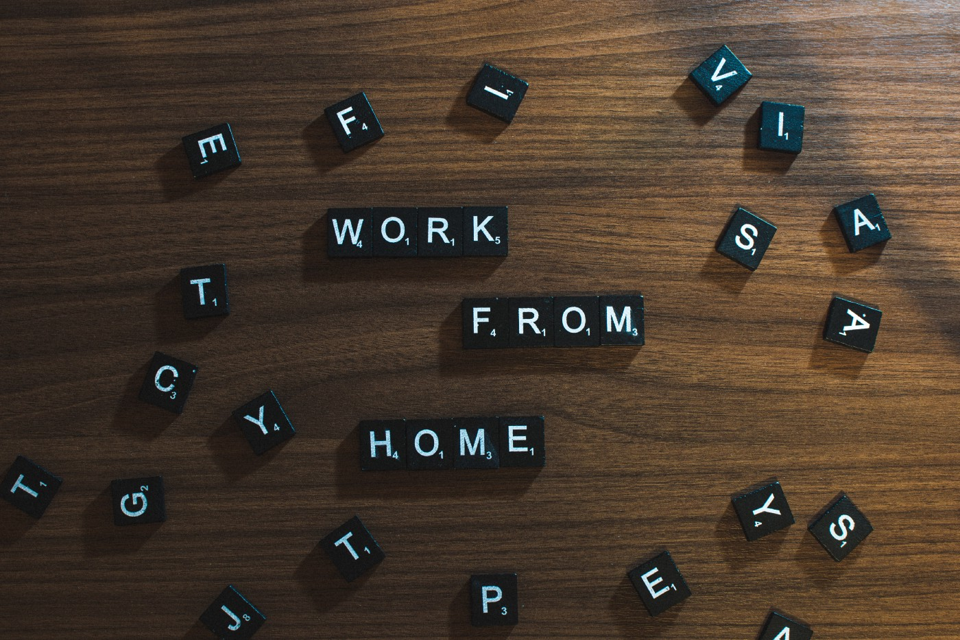"""Scrabble letters on a table. They spell out """"Work from home."""""""