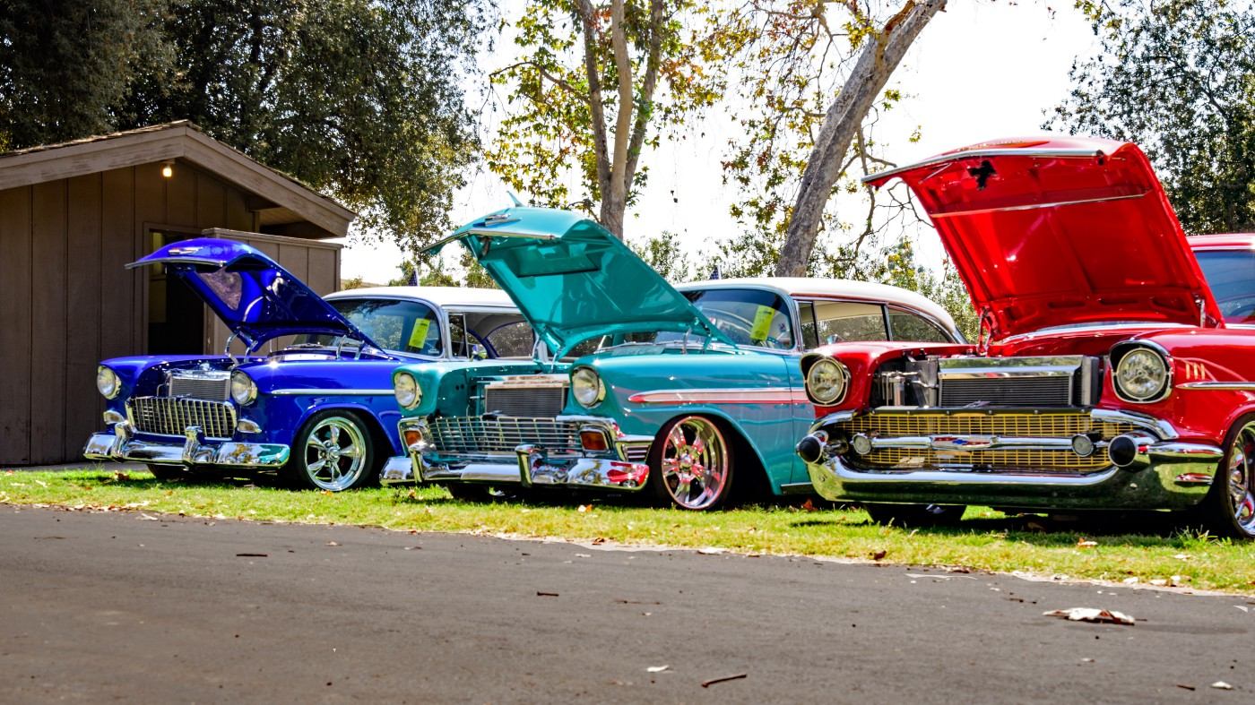 Three antique cars with their hoods up