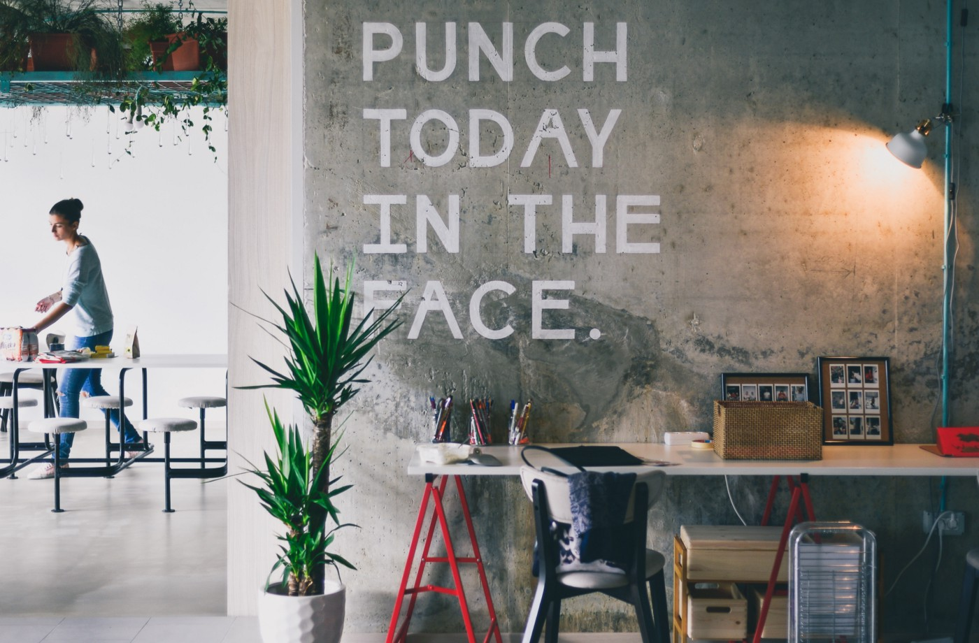 Office environment with the quote 'punch today in the face' written on the wall