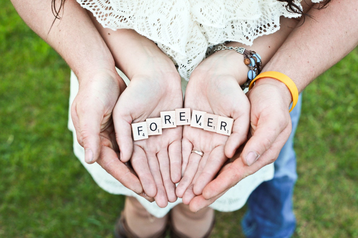 "A couple holding scrabble letters that spell out the word ""forever"""