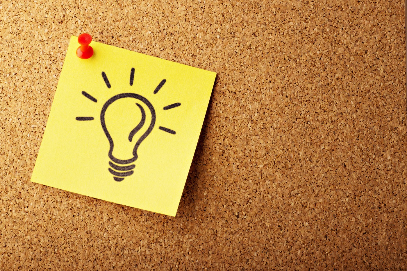 A sticky note with a light bulb drawn on it pinned to a bulletin board.