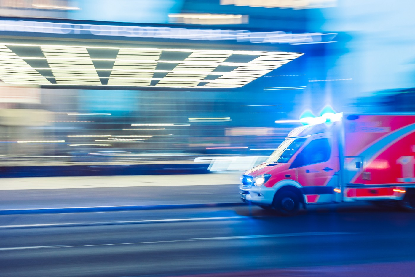An ambulance speeding down the road. The photo is a bit blurry to show the action.