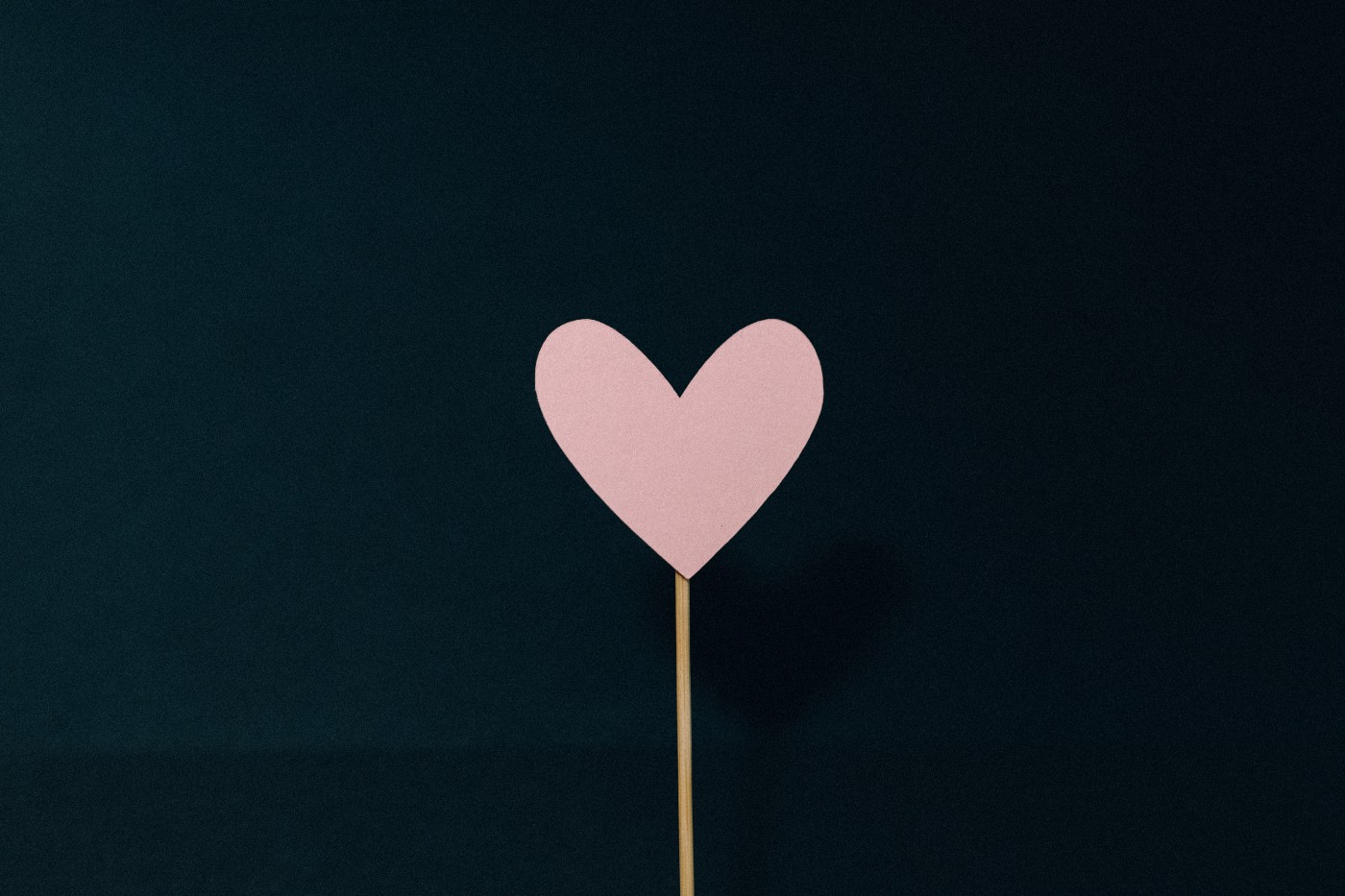 Pink paper heart on black background