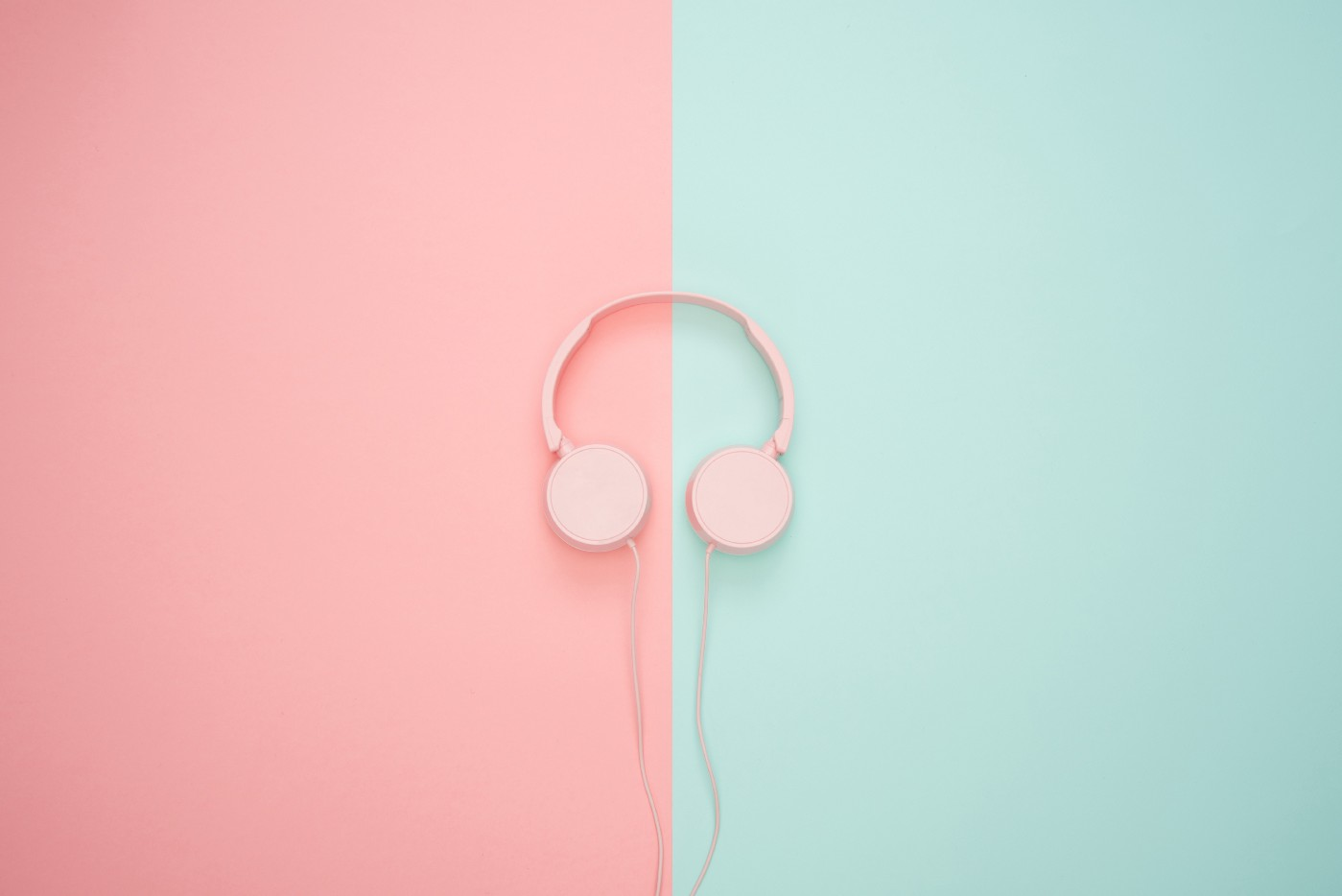 A pink headphone on top of colorful background split into pink and turquoise.