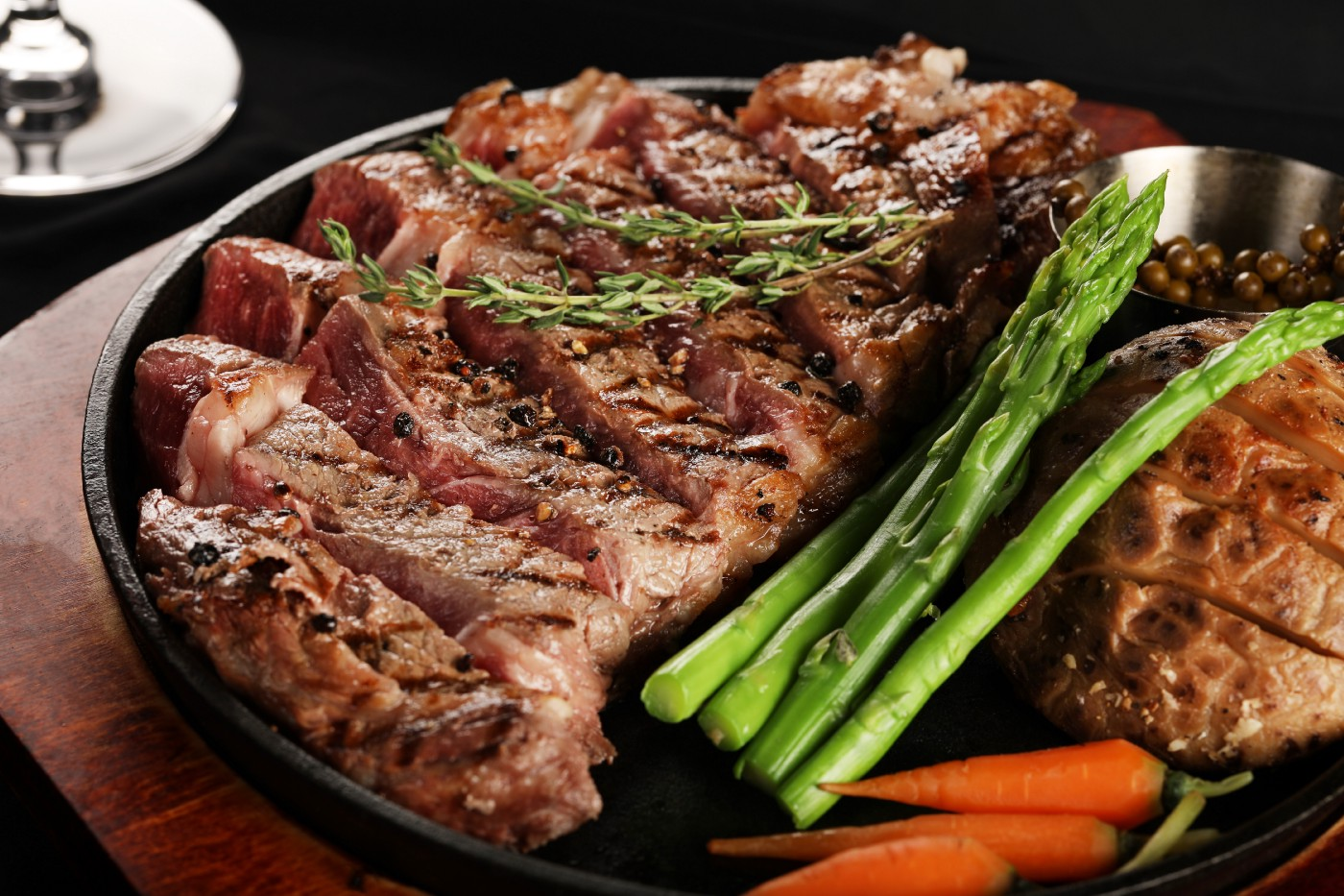 A big beef steak dinner with asparagus and carrots