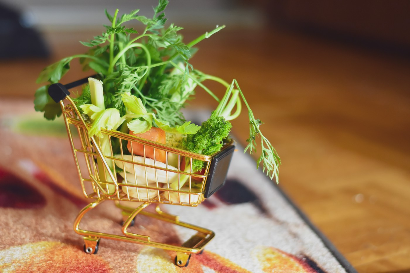 Tiny shopping cart filled with bits and pieces of vegetables.