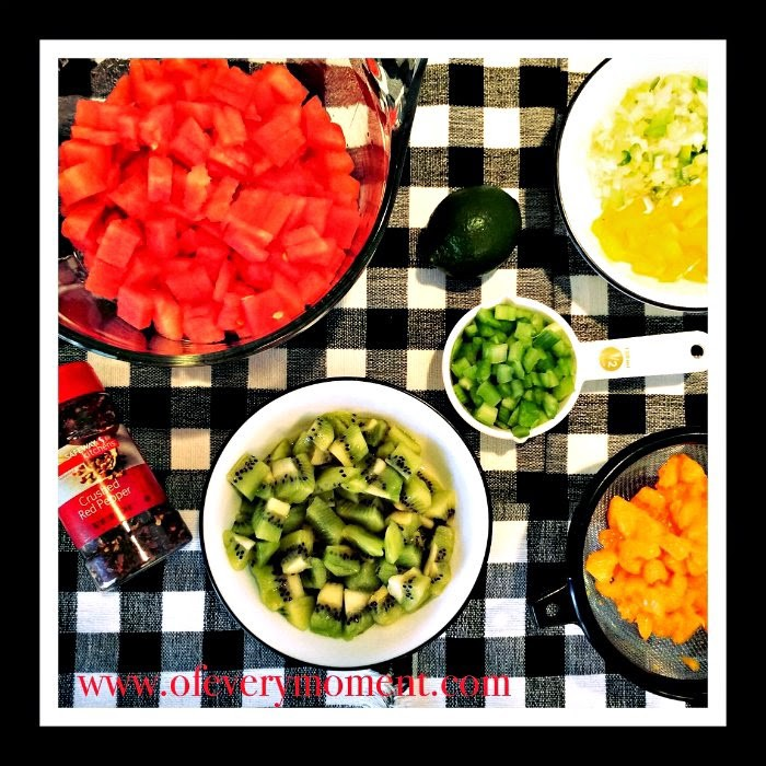 Ingredients for watermelon salsa, in bowls placed on a black and white checkered cloth.