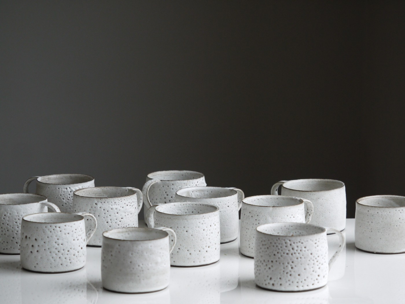 White mugs on a shiny white table, against a black background. The mugs have irregular shapes.