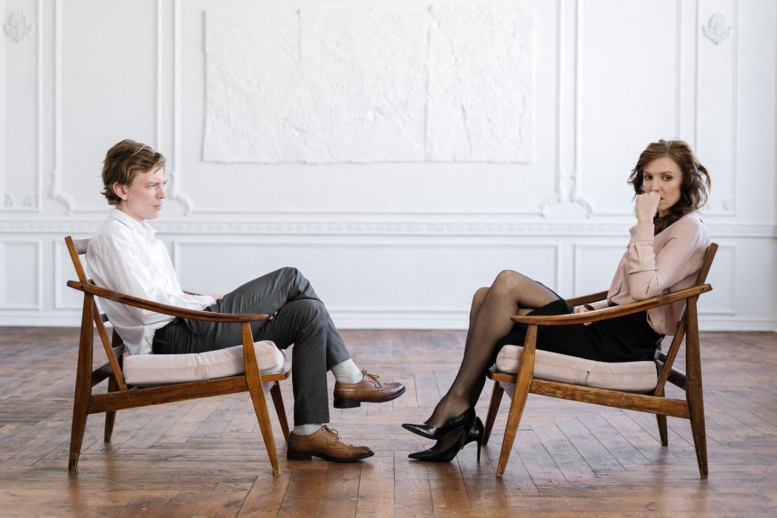 Two people sit in chairs across from each other. One seems unsure or uncomfortable, looking away while the other stares. #therapy