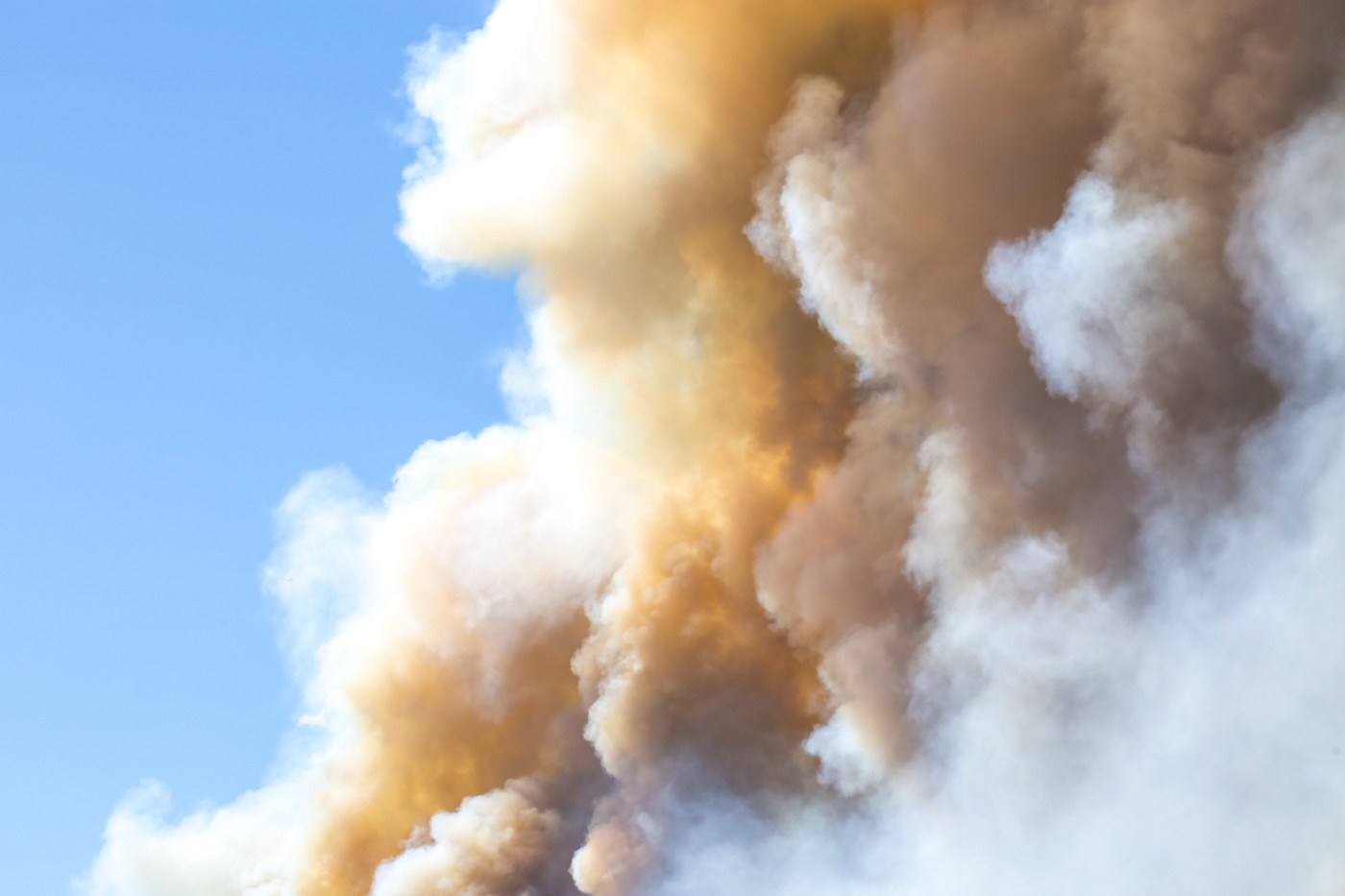 photo of smoke, steam and ash rising from a fire against blue sky