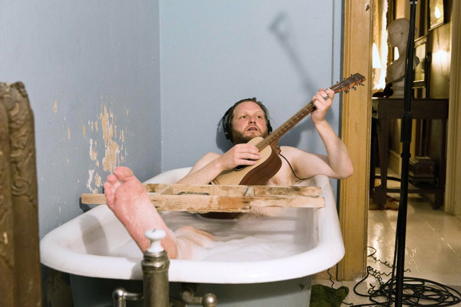 A video still of Ragnar Kjartansson in a full bathtub playing the guitar and wearing headphones.