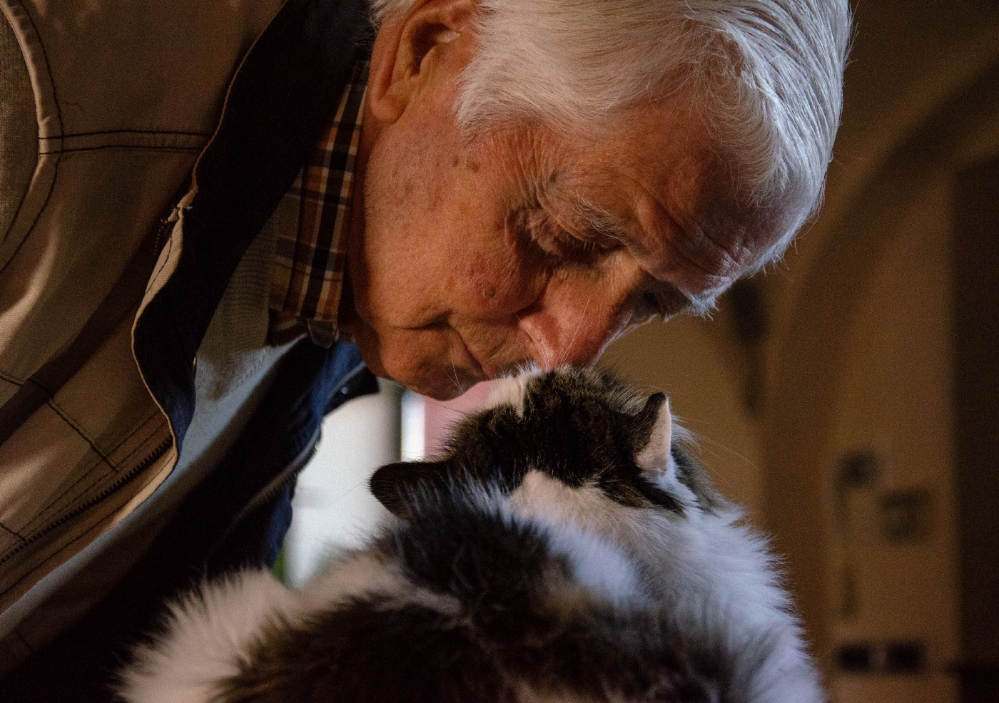 An older man rubs noses with a cat.
