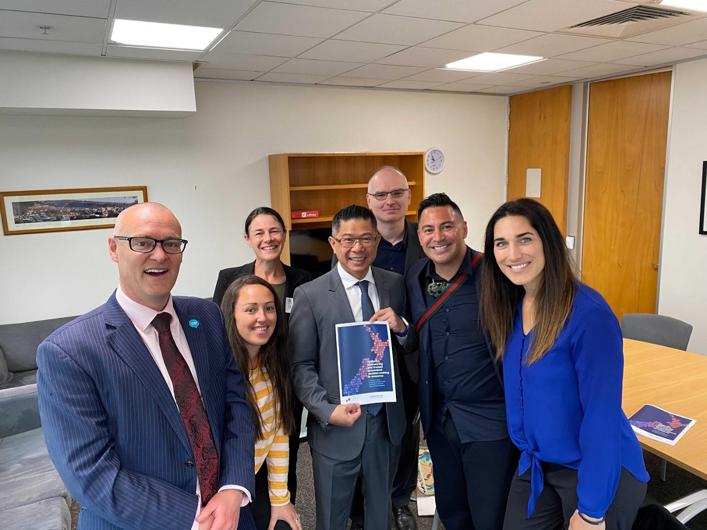 The Minister and Council members grouped together smiling at the camera. Mitchell Pham in centre holds a copy of the report.