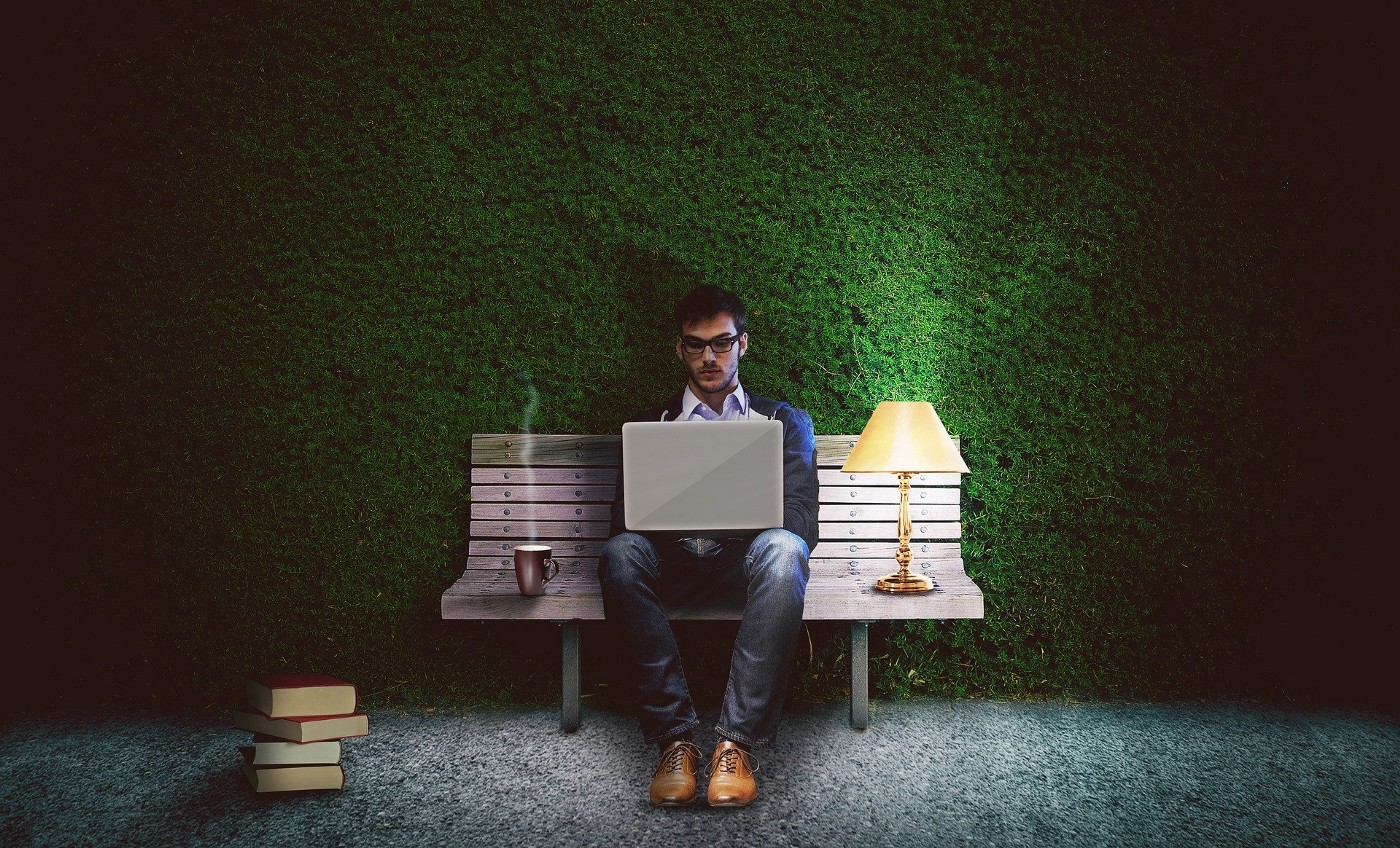 A man is sitting on a bench in a park, typing on a laptop. There's a coffee and a lit lamp next to him.