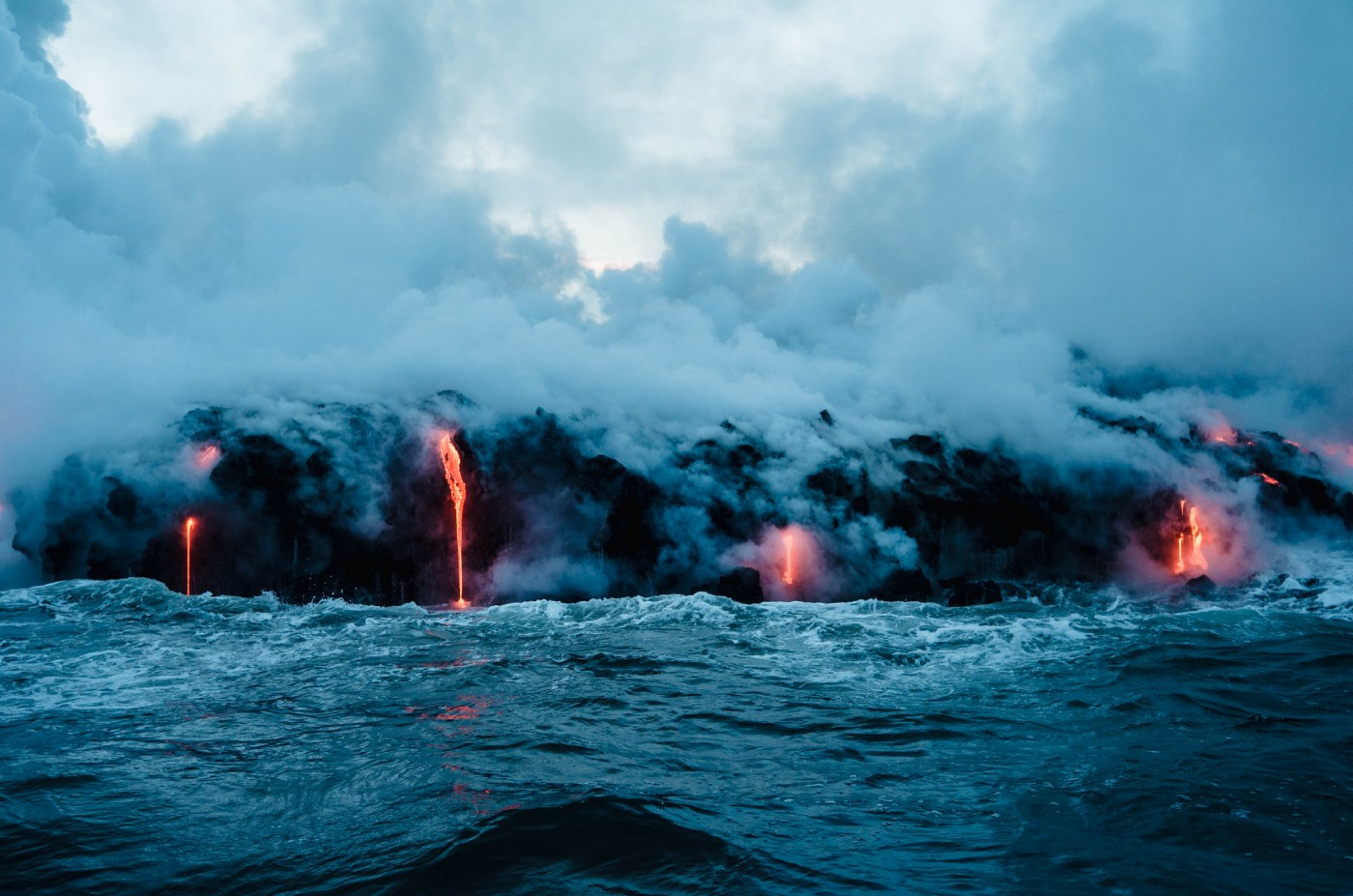 Image of hot lava pouring into the ocean on a stormy day