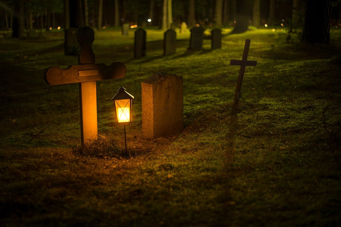 An image of several gravestones in a graveyard at night. A lantern glows gold in the foreground and lights the stones.