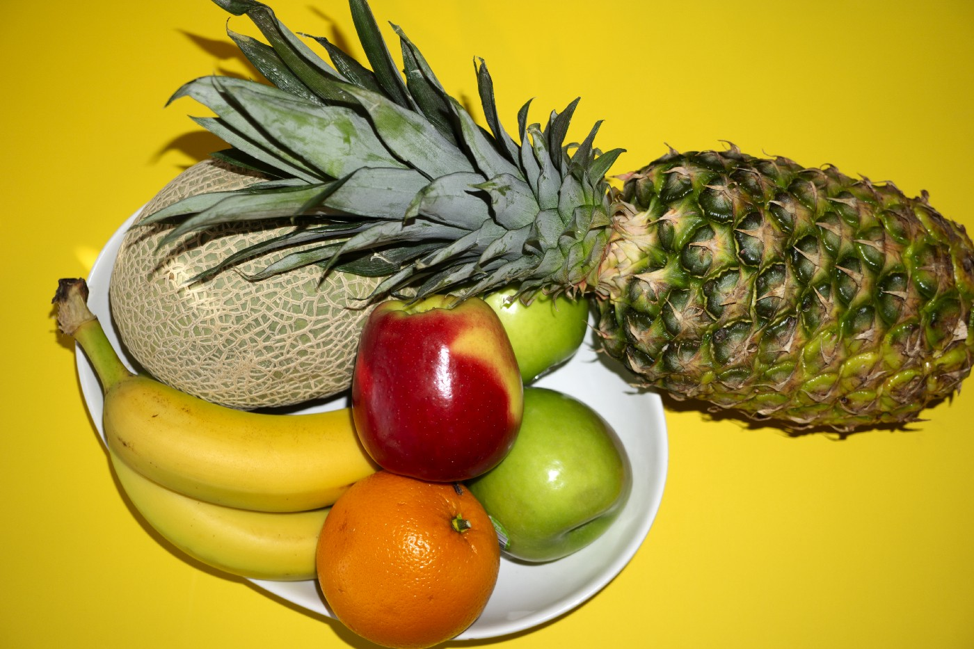 A fruit bow with apples, (red and green) oranges, bananas, a melon and a pineapple.