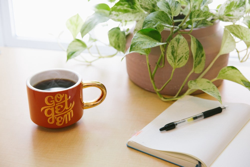 Coffee mug with quote 'Go get them', diary with pen motivating to start writing