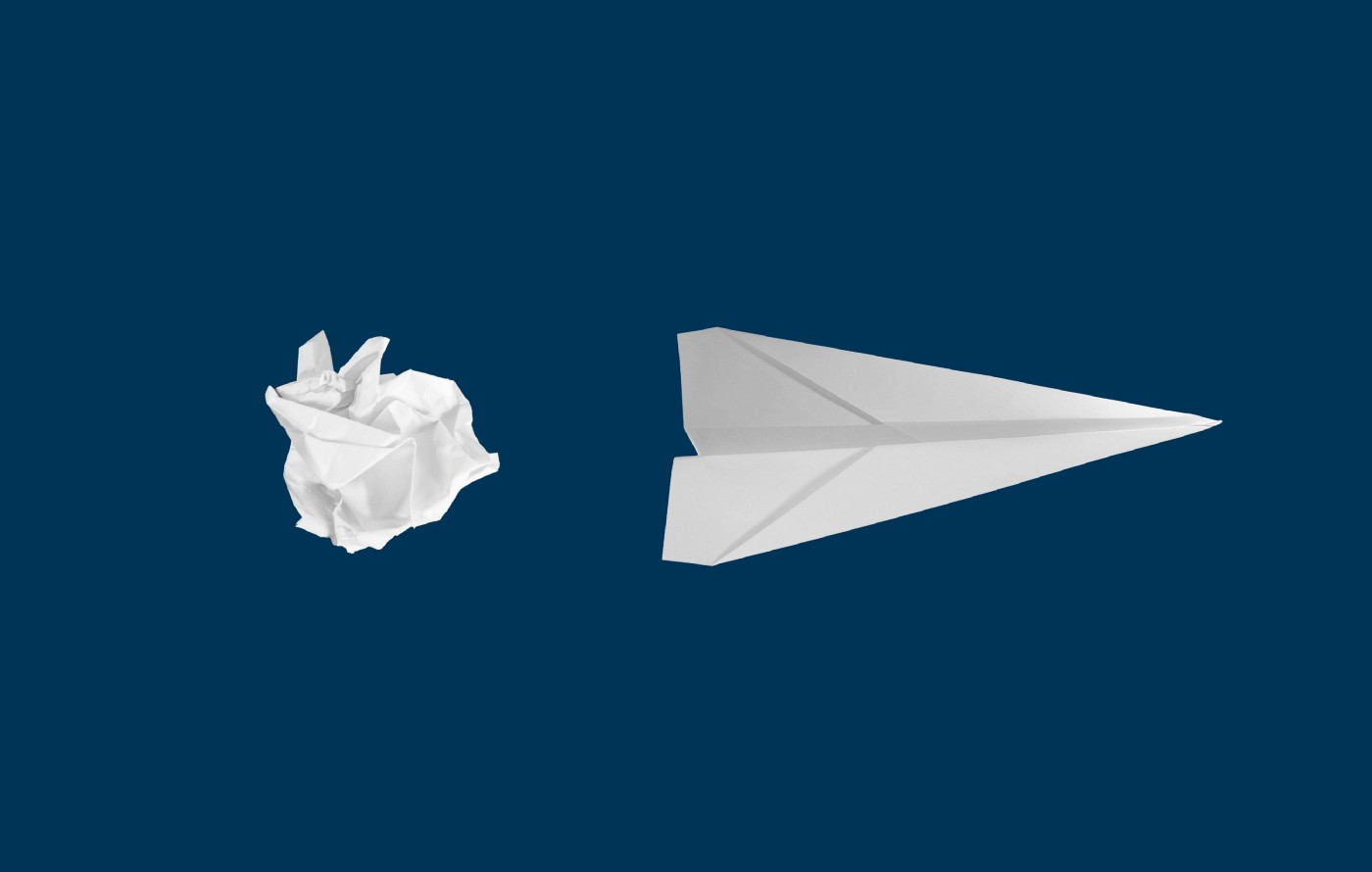 Crumpled paper next to a paper airplane