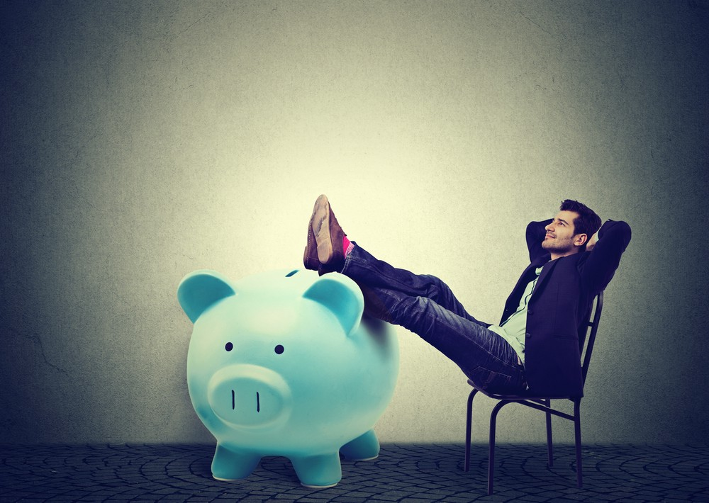 Financially successful business man sitting in chair and relaxing with his legs on a huge piggy bank. It's an image to represent financial security and contentedness.