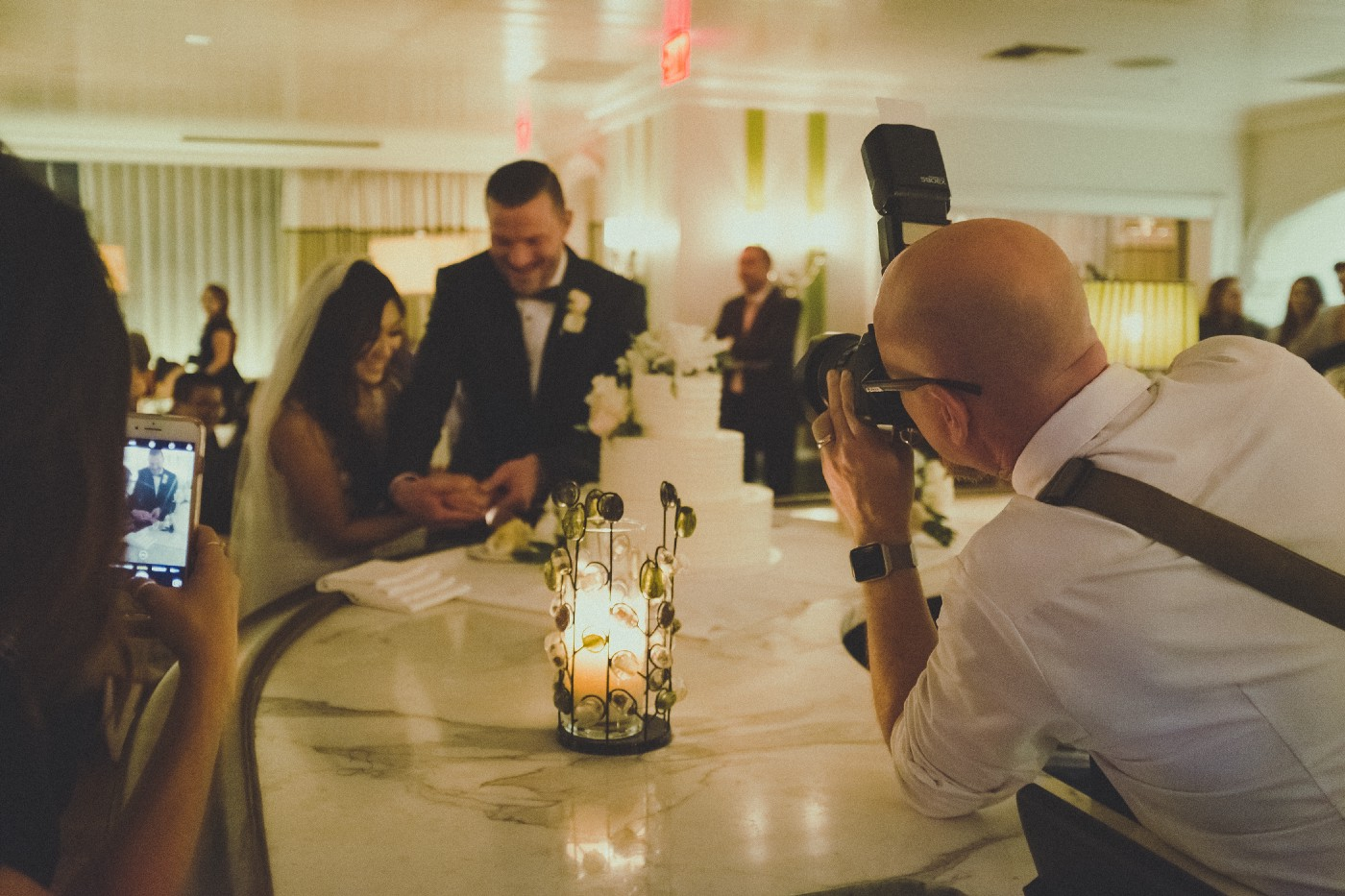 A photographer taking a picture of a bride and groom cutting the cake at their wedding reception.