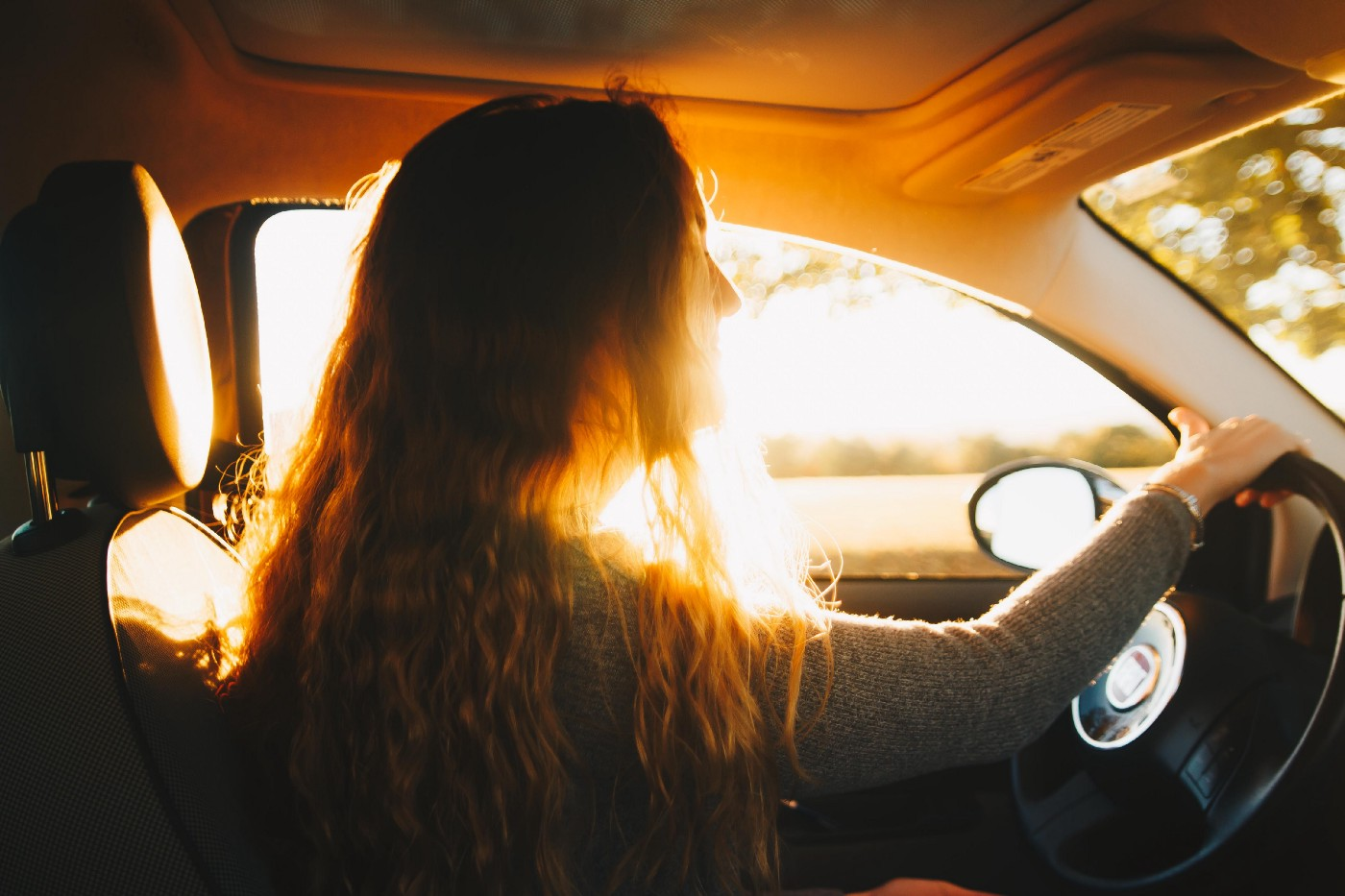 Golden light framing a long haired girl at the wheel of a car