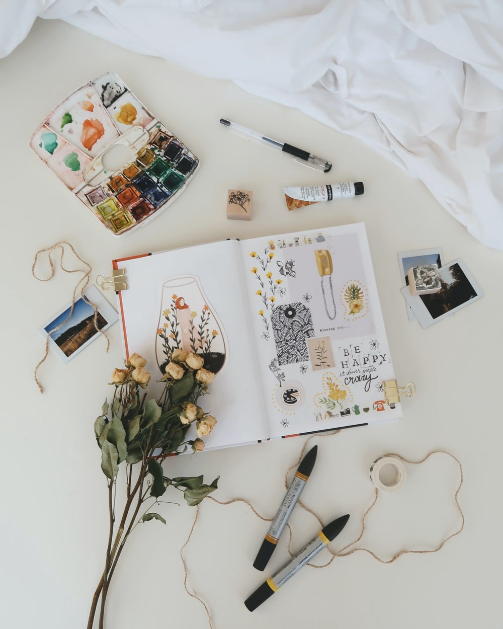 Journal with paints and dried flowers and polaroid pictures