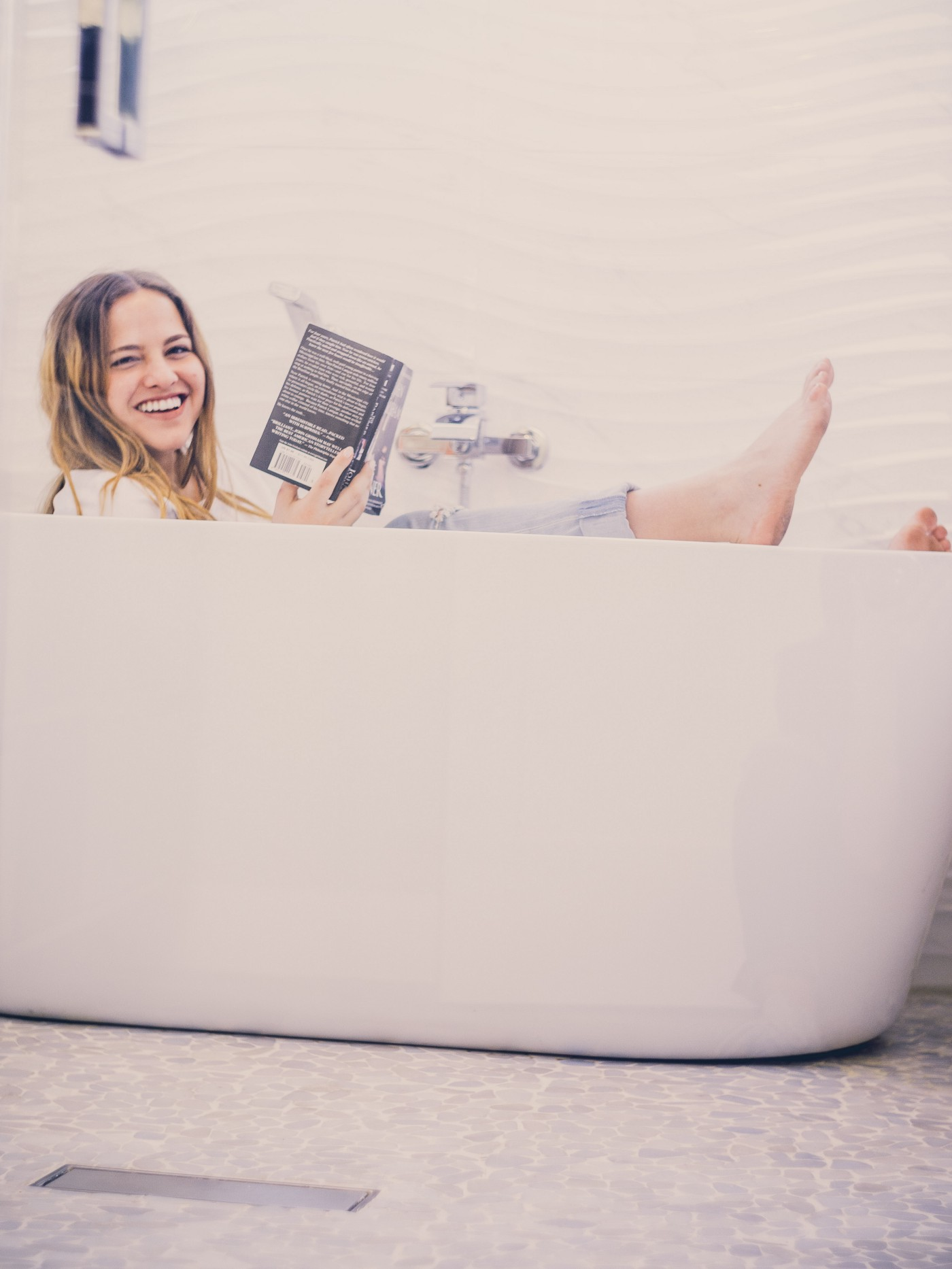 Young woman holding a book while sitting in a white bath tub