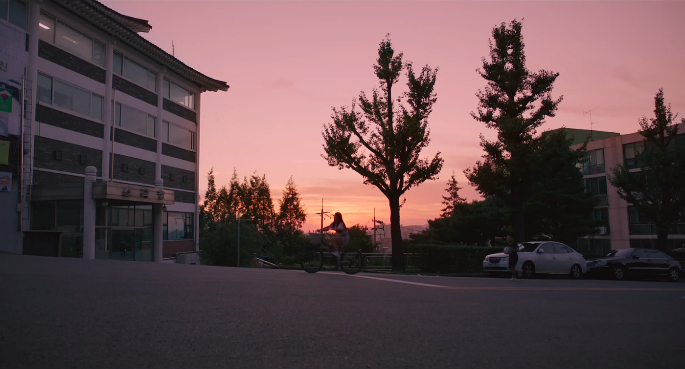 Film still from MOVING ON, of a driveway, trees, and a character on a motorbike silhouetted against a pink sunset sky.