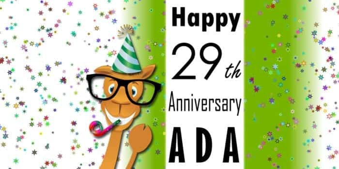 """Seymour, wearing a party hat, blowing a noise maker, and pointing to the words, """"Happy 29th Anniversary ADA"""""""