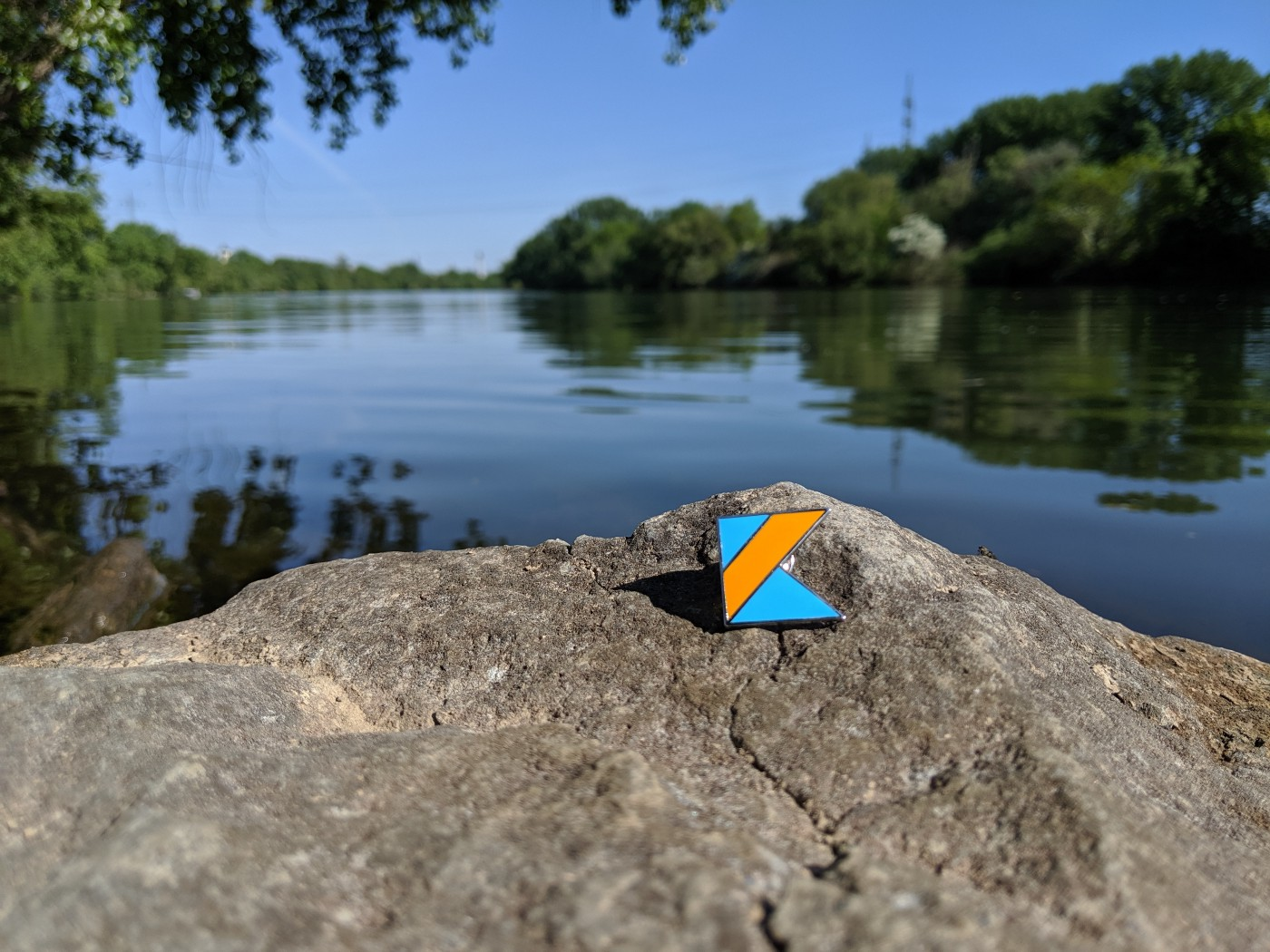 Kotlin logo on a rock by a lake