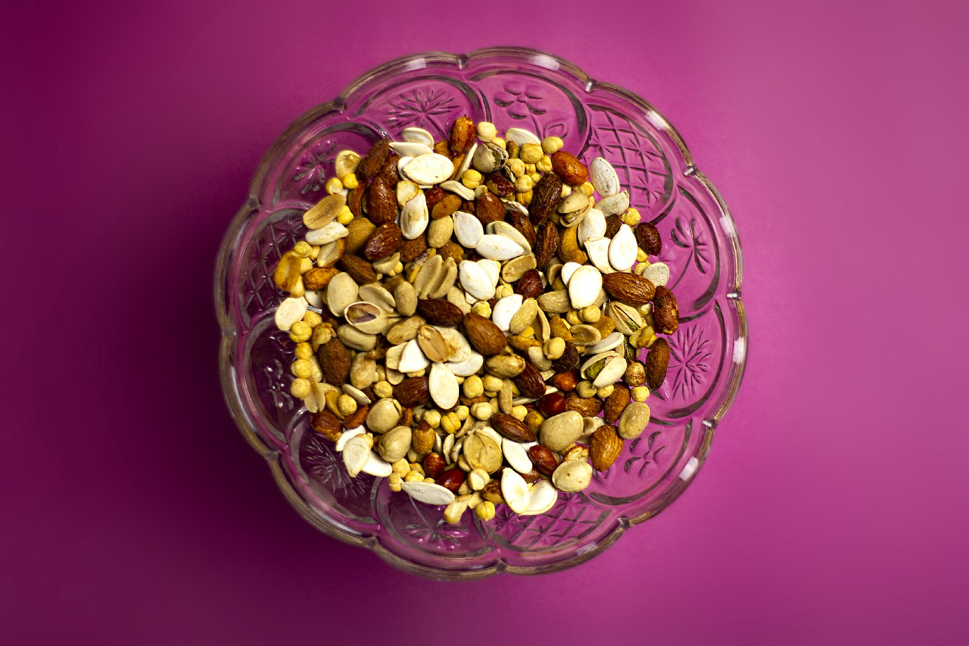 a glass bowl of nuts and dried fruit sitting on a colorful background