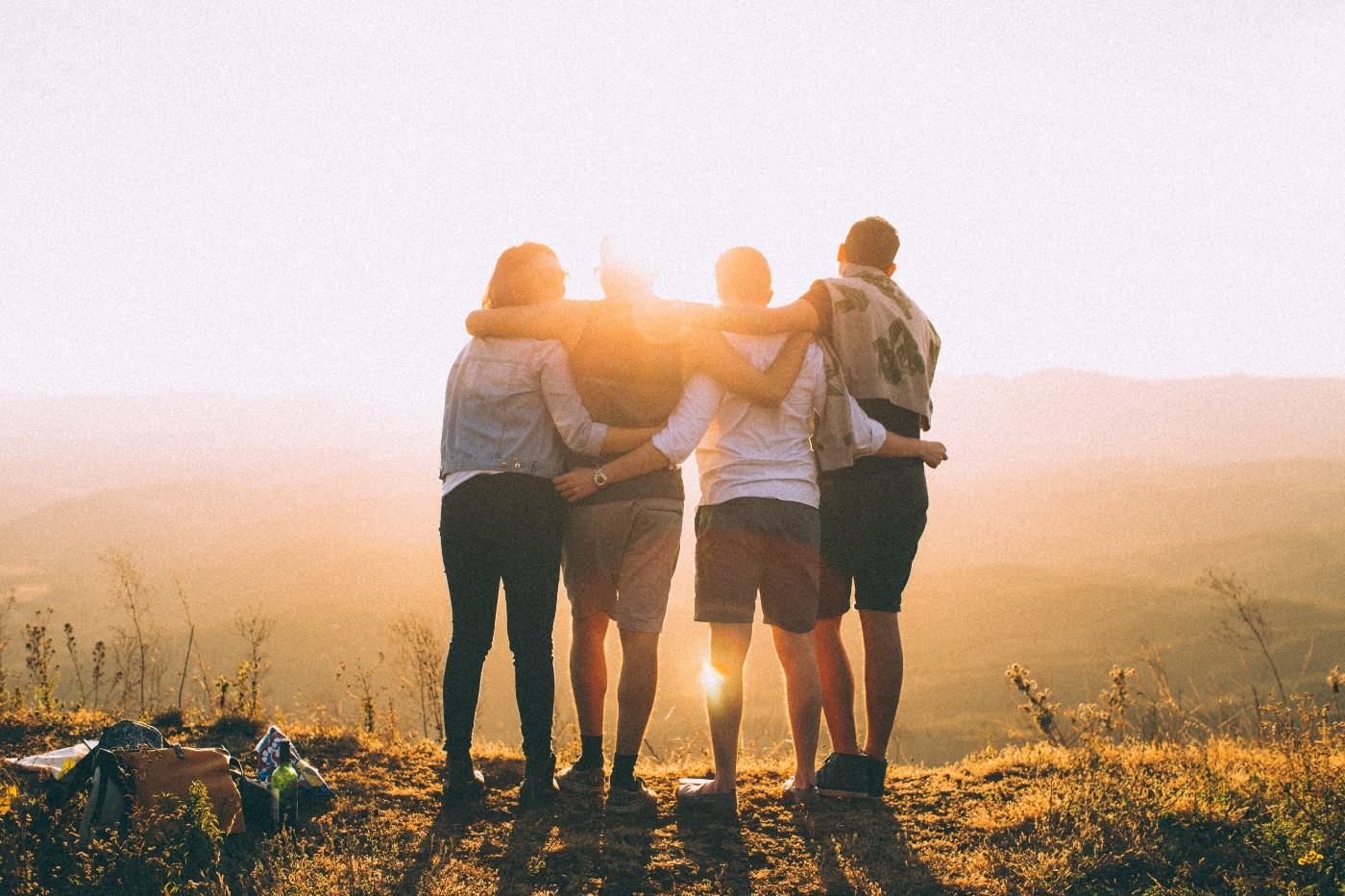 Four people stand on a hilltop with their arms around each other's waists, watching the sun set.
