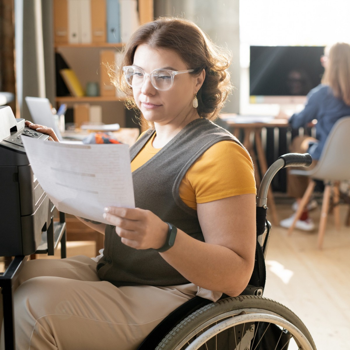 Woman with short brown hair sits in a wheelchair looking at a piece of paper, with her other hand on a desk she is sitting in front of with a printer.