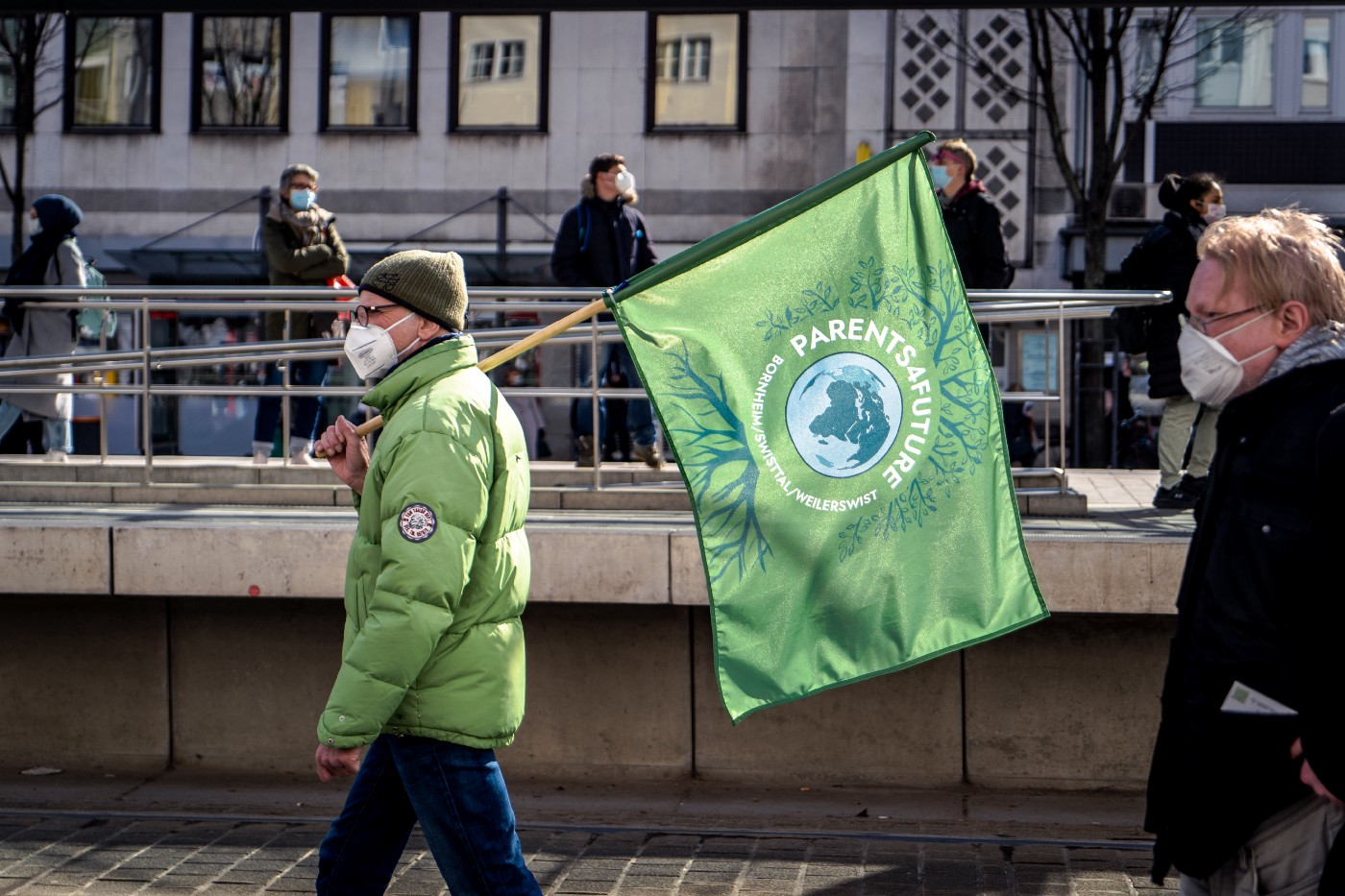 """A person in a green jacket holding a green flag that reads:""""PARENTS 4 FUTURE""""."""