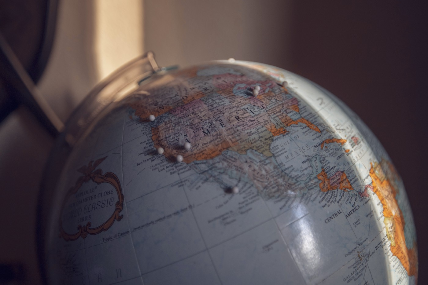 A large globe with stick pins designating travel destinations