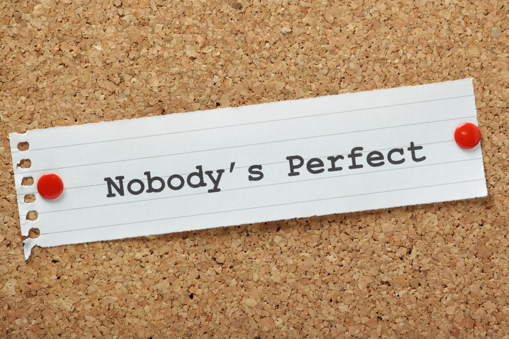 The phrase Nobody's Perfect typed on a piece of paper pinned to a cork notice board. A concept for self improvement or acceptance that we all have flaws but this does not make us any less equal
