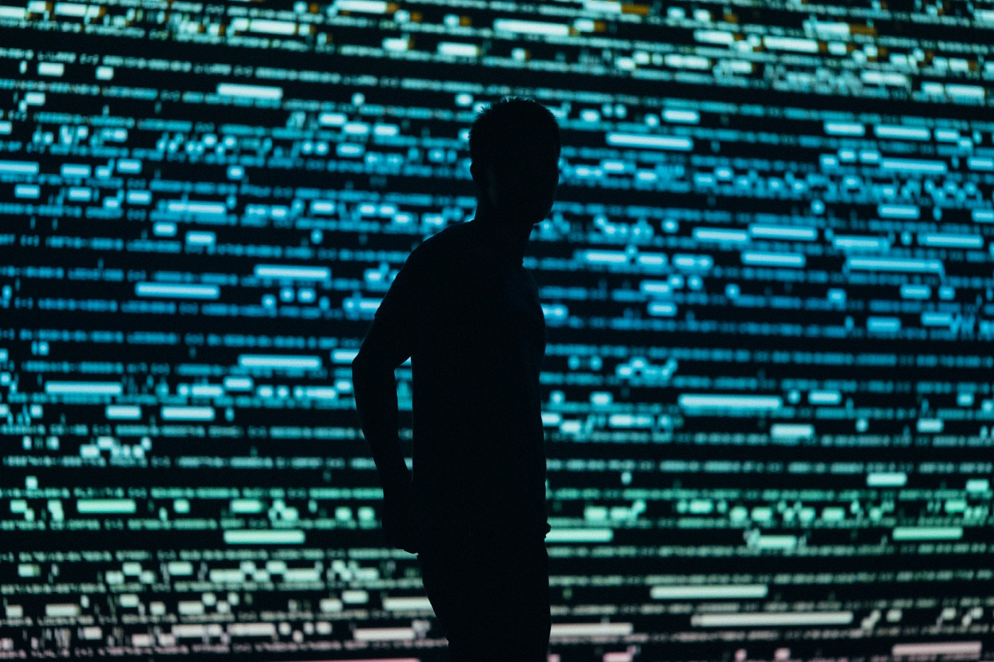 Man standing in front of wall of data