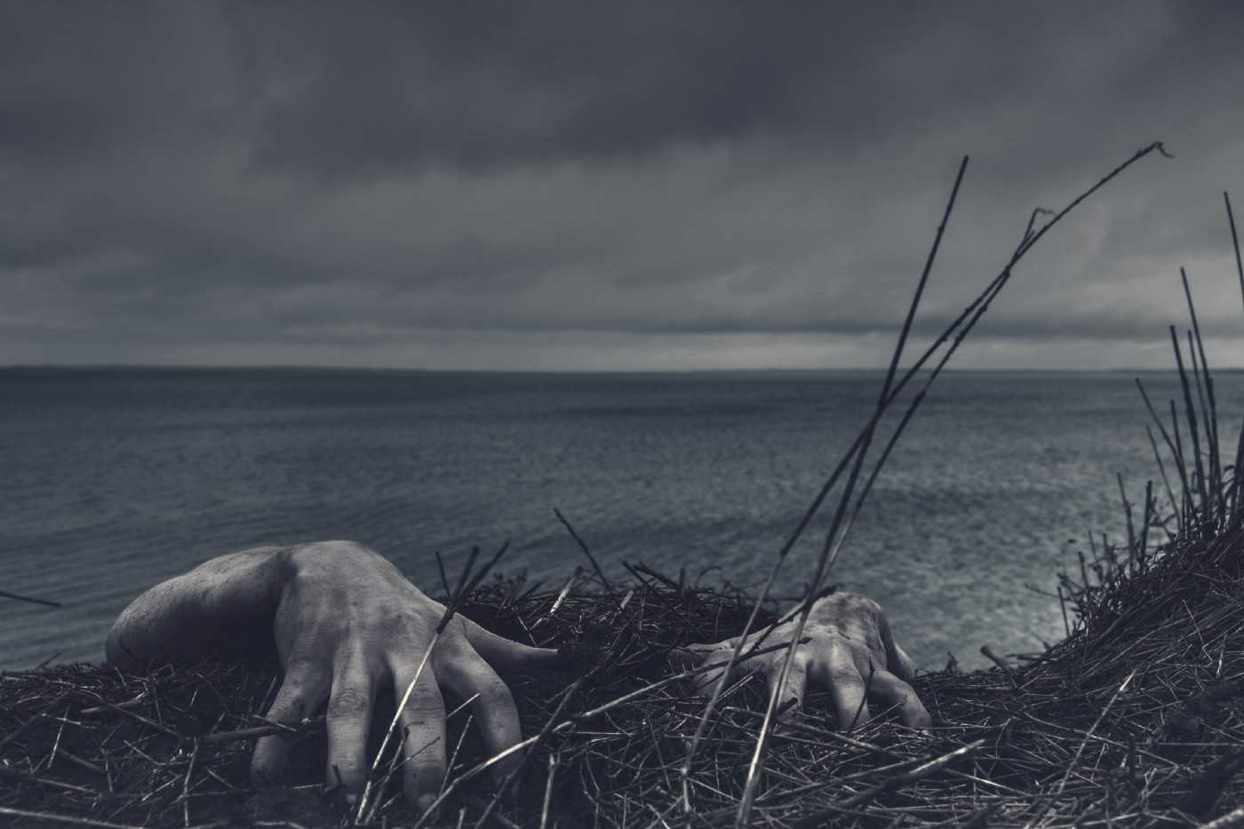 Photo of scary hands reaching up over a cliff